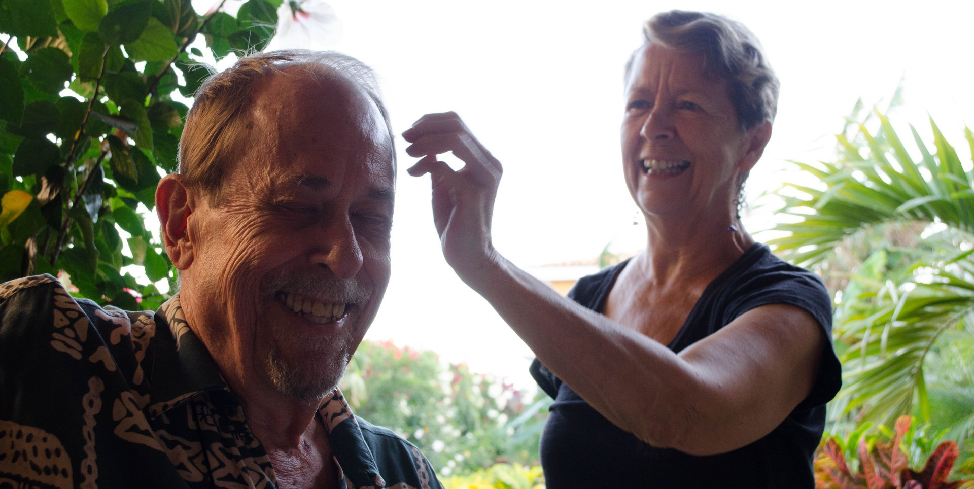 Carol Lynch fixes her husband Jim's hair in their backyard in Granada, Nicaragua. The Lynches are American expatriates who moved to Nicaragua in 2010. (Photo by Amanda LaCasse)