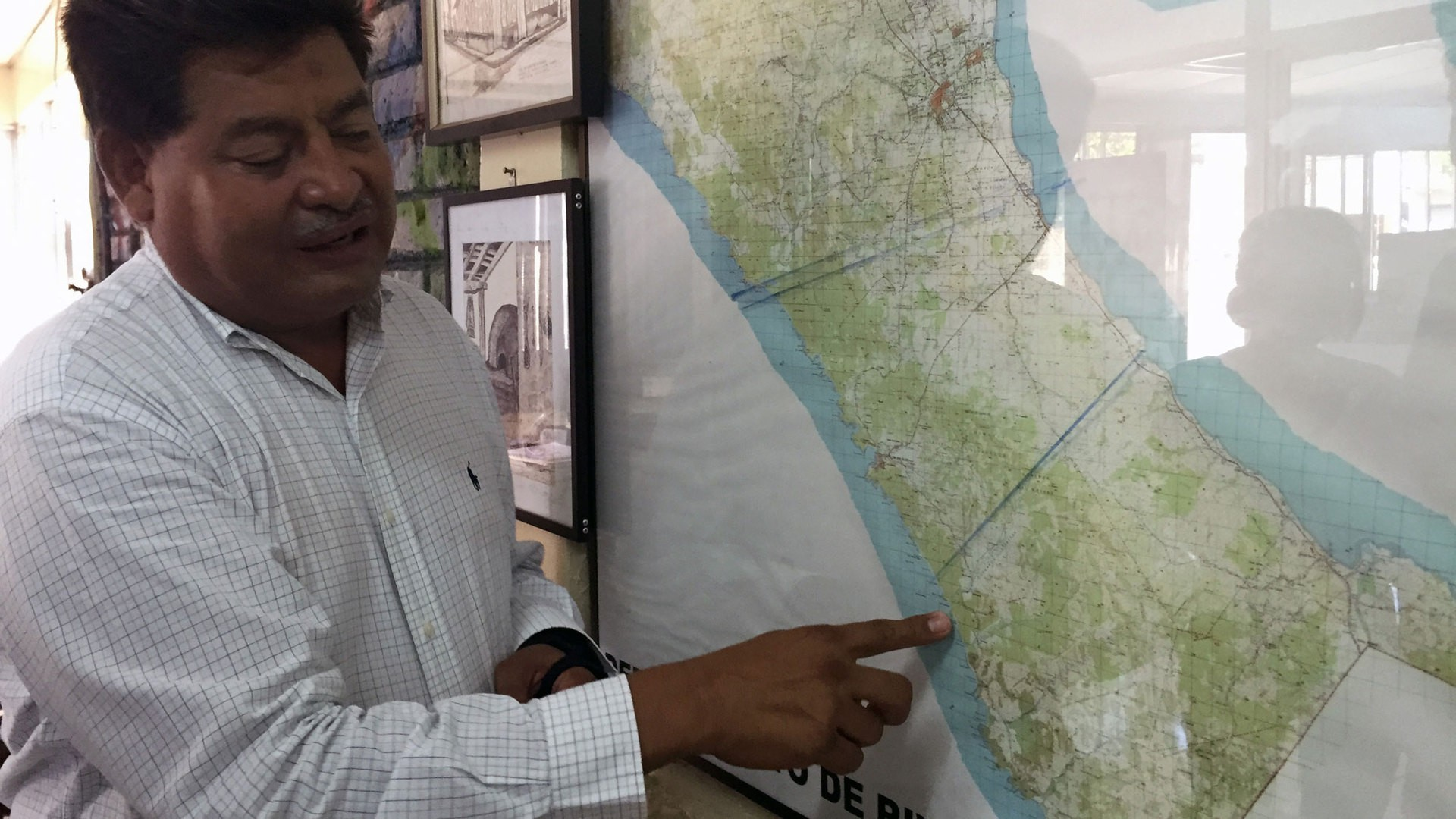 Ortega points at proposed canal routes on a map of Nicaragua. (Photo by Miguel Otárola)