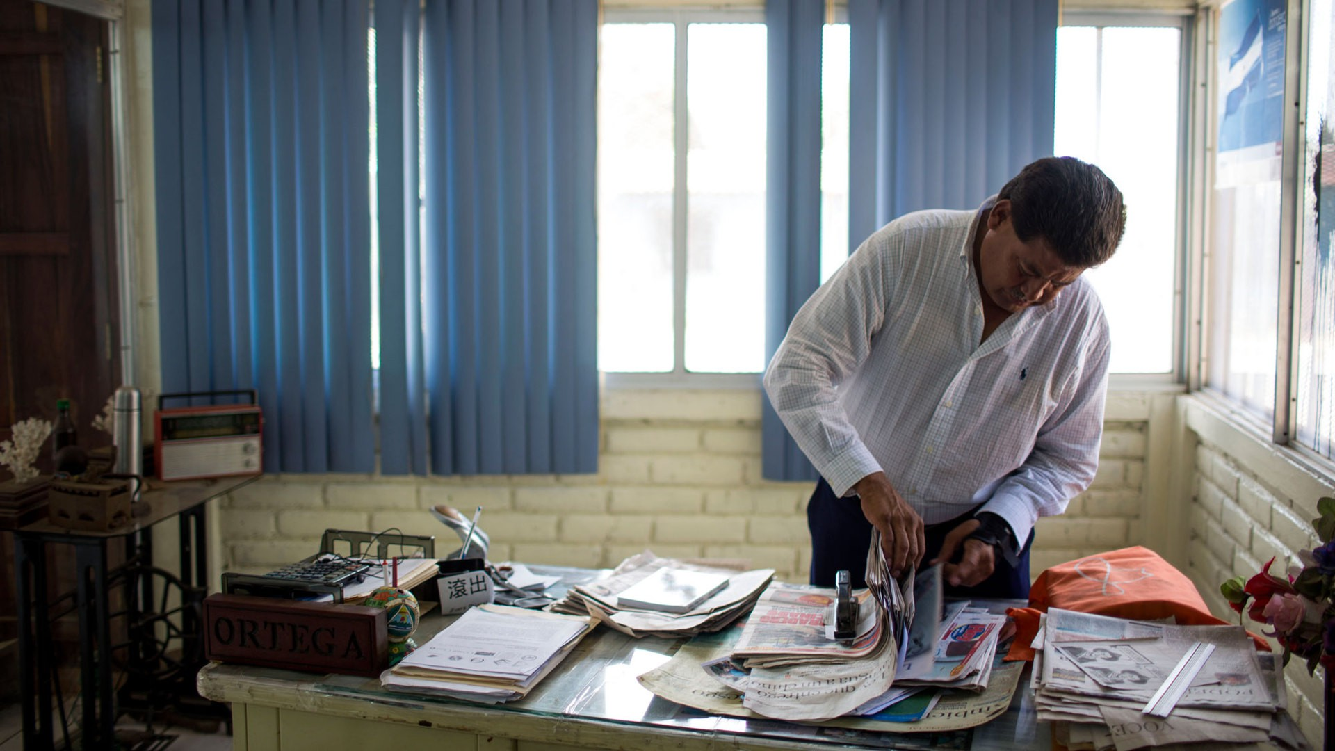 Ortega sifts through newspaper clippings in his office at FUNDEMUR. (Photo by Dominic Valente)