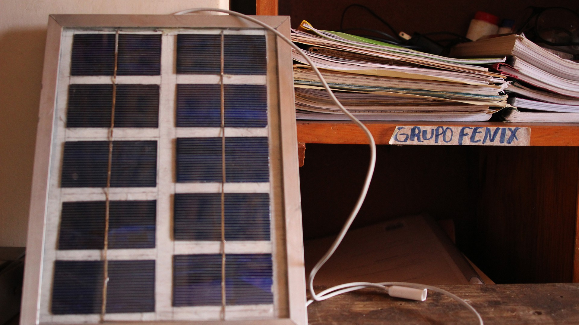 A solar cellphone charger stands beside a set of cubbies used for organization in the Grupo Fénix building at the Solar Center in Sabana Grande, Nicaragua, on March 9, 2015. International students build a charger like this when they visit in preparation for building a larger panel to install on someone's home. Students can keep this solar charger when they leave. (Photo by Molly Bilker)