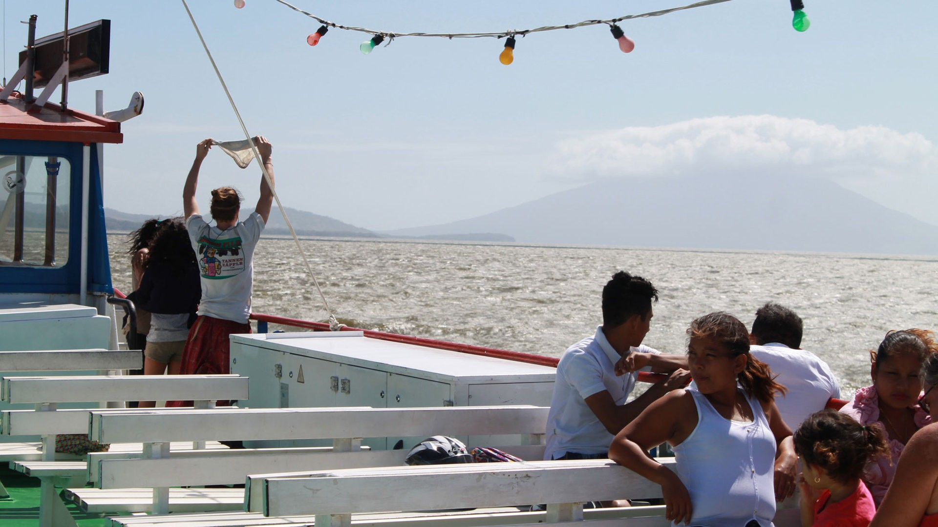 Tourists view the volcanoes of Ometepe, Nicaragua, from a boat. (Photo by Sara Weber)