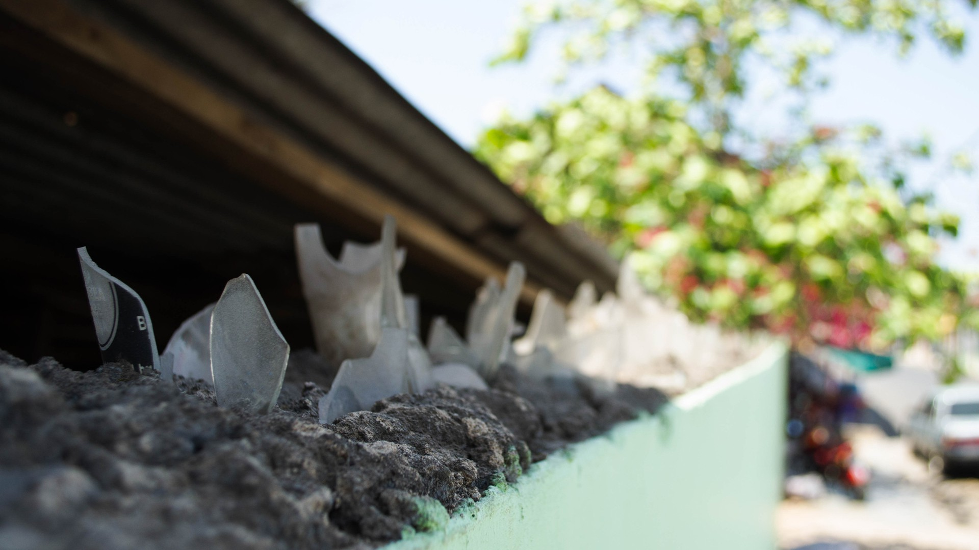 Broken bottles are cemented to the top of a wall at a house in Granada, Nicaragua.  (Photo by Amanda LaCasse)