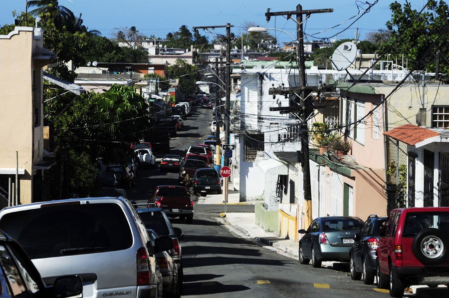 ... The street outside the home of Joel Féliz de Jesus is narrow and filled with cars ...