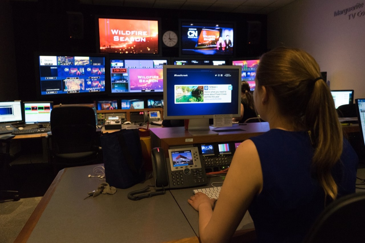 A producer looks at screens in the control room.