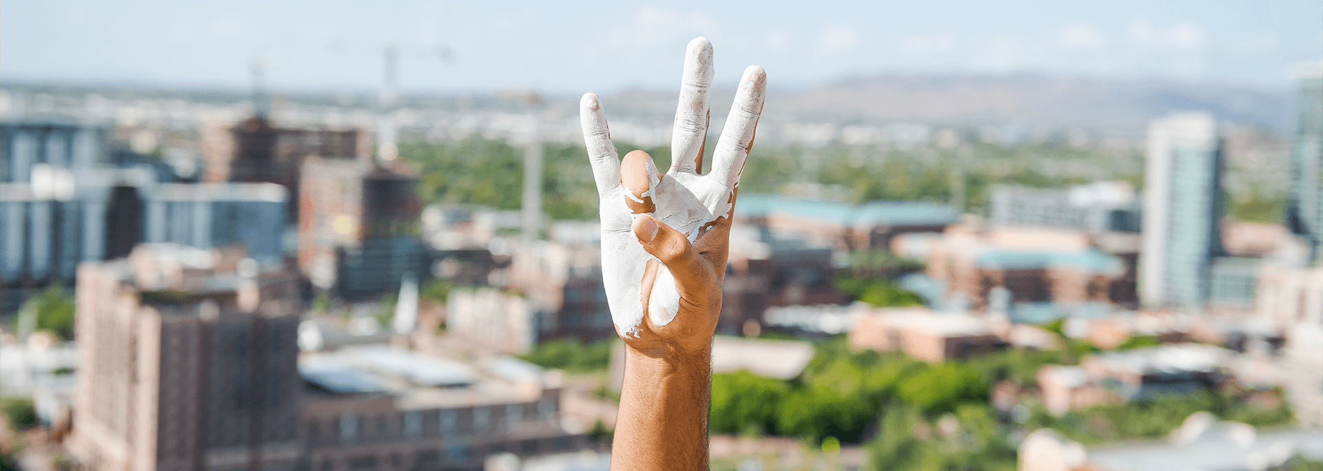 A hand covered in paint holding up the Sun Devil pitchfork sign in front of a city background.