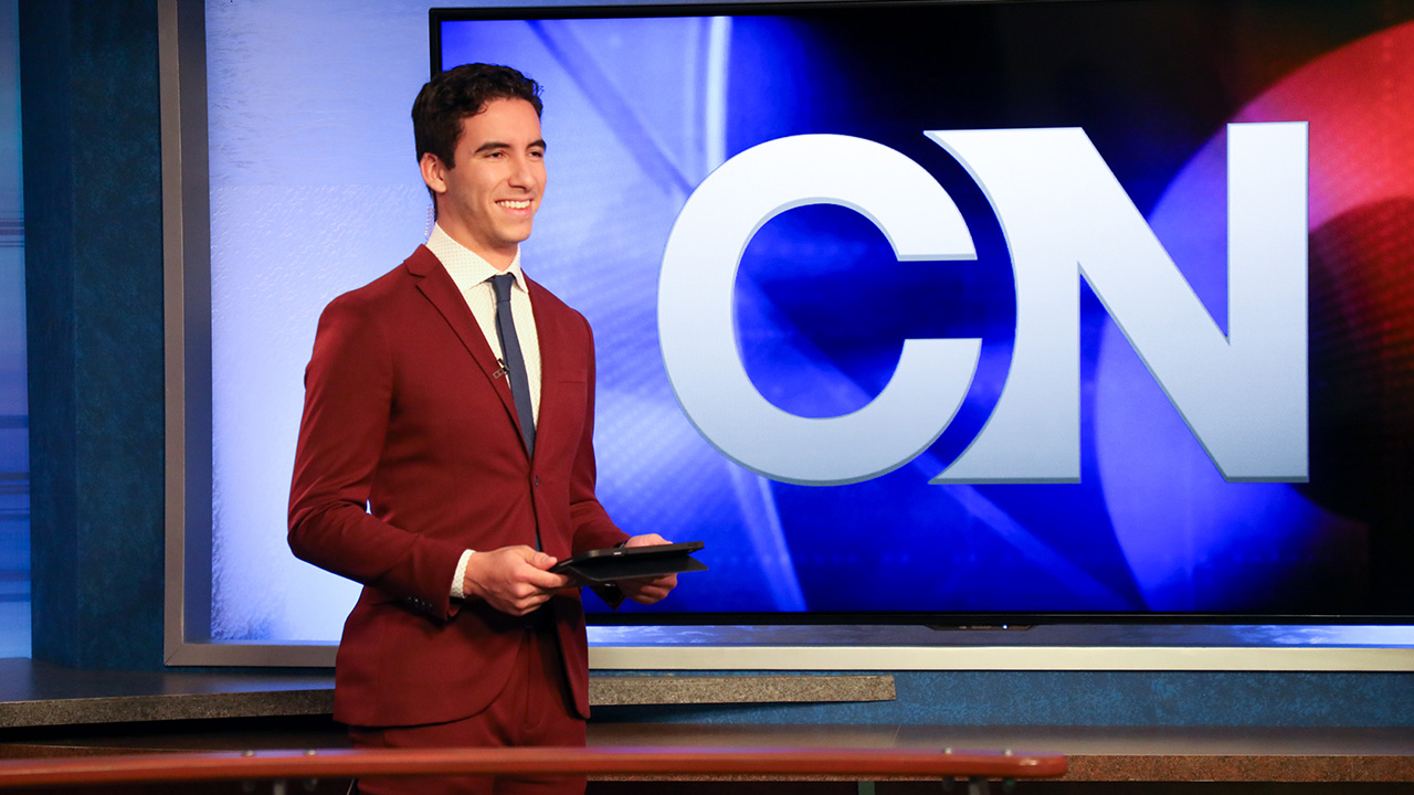 A student delivers the new in front of the Cronkite News screen.