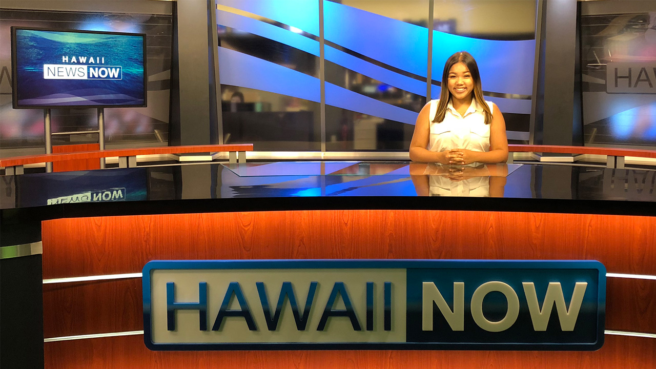 A student intern sitting at the Hawaii Now news desk.