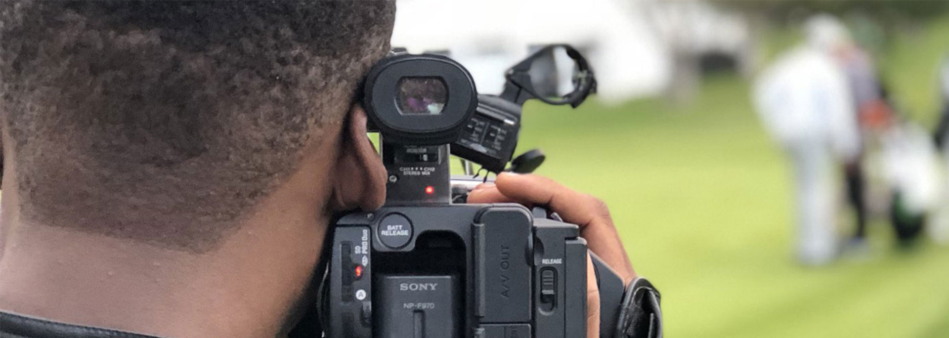 A student holds a broadcast camera.