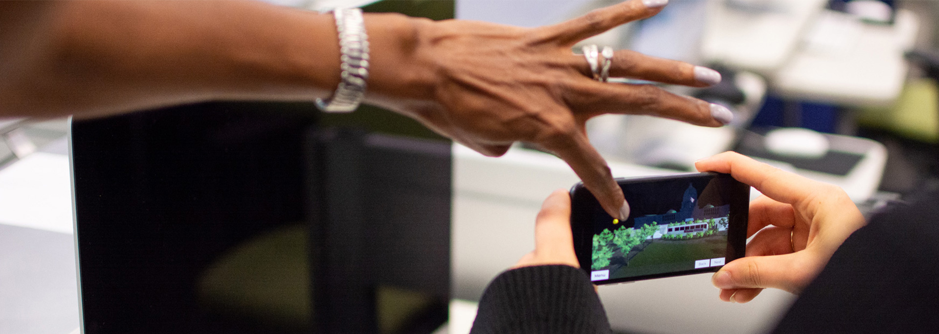 A student holds their hone while the instructor points to the screen.