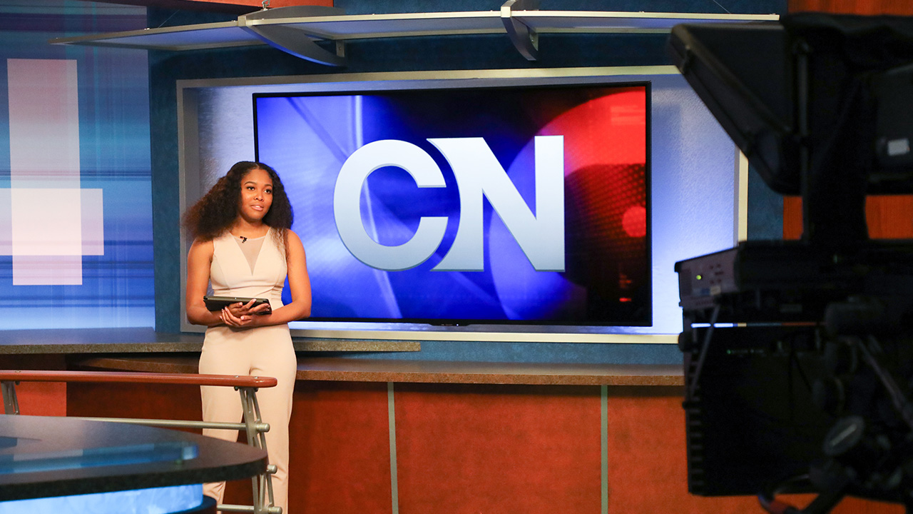 A student delivers a newscast in front of cameras in Cronkite News.