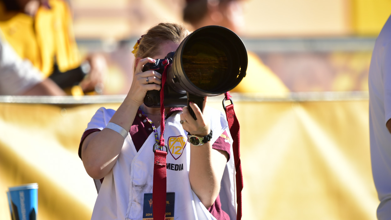 A student photographs a sporting event.
