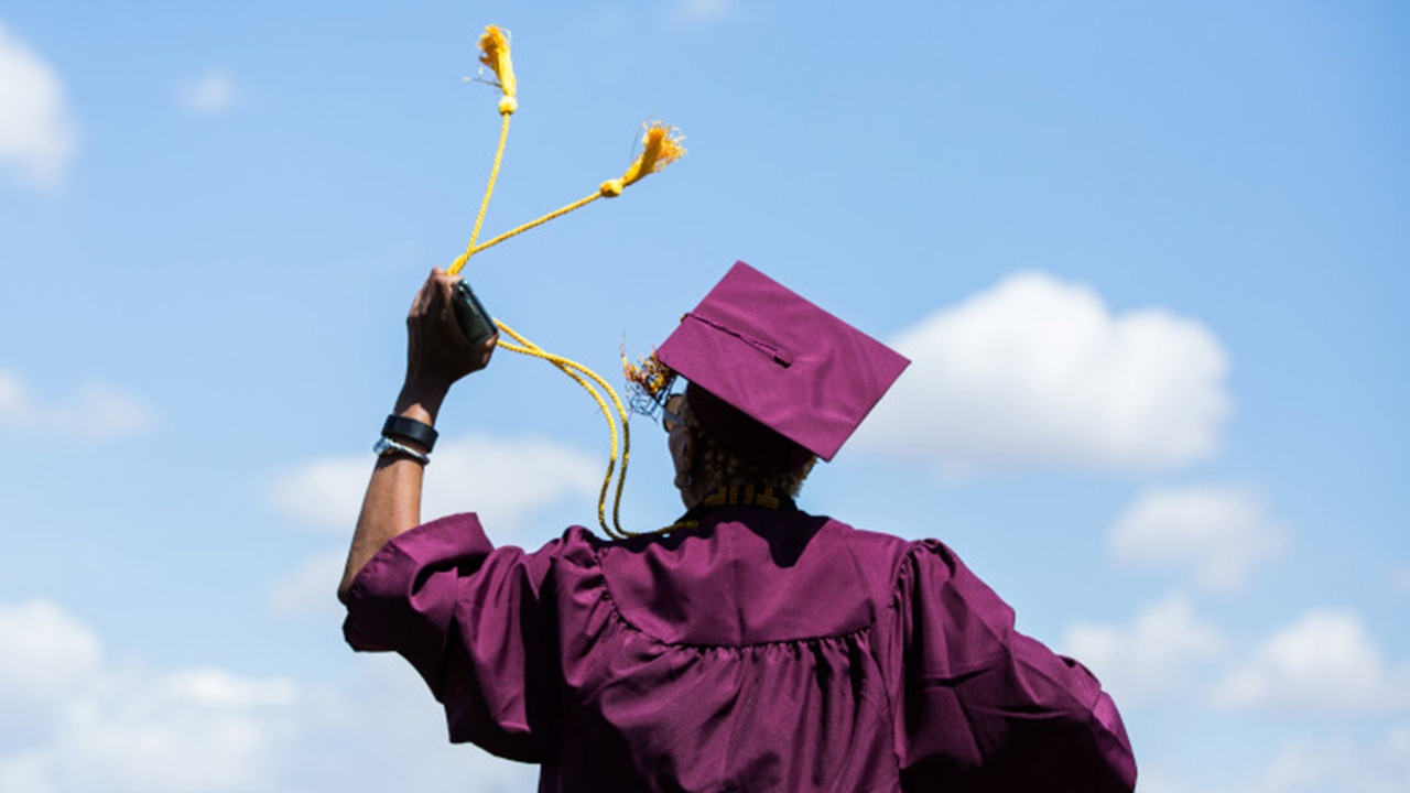 A new graduate celebrates her graduation by standing on a chair and twirling her cords.
