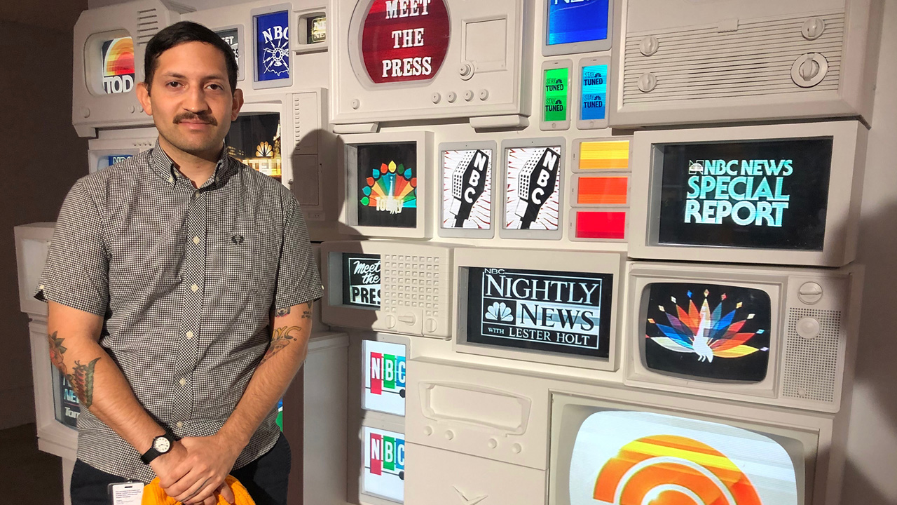 A student stands in front of vintage tv screens that show the NBC logo.