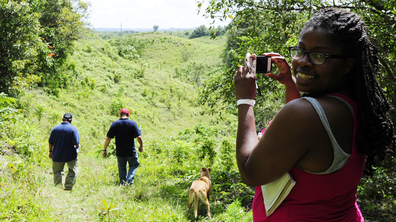 A student takes photos in a jungle.