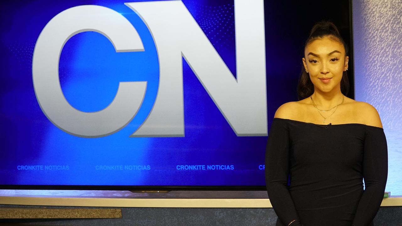 A Cronkite Noticias student stands next to the Cronkite News logo.