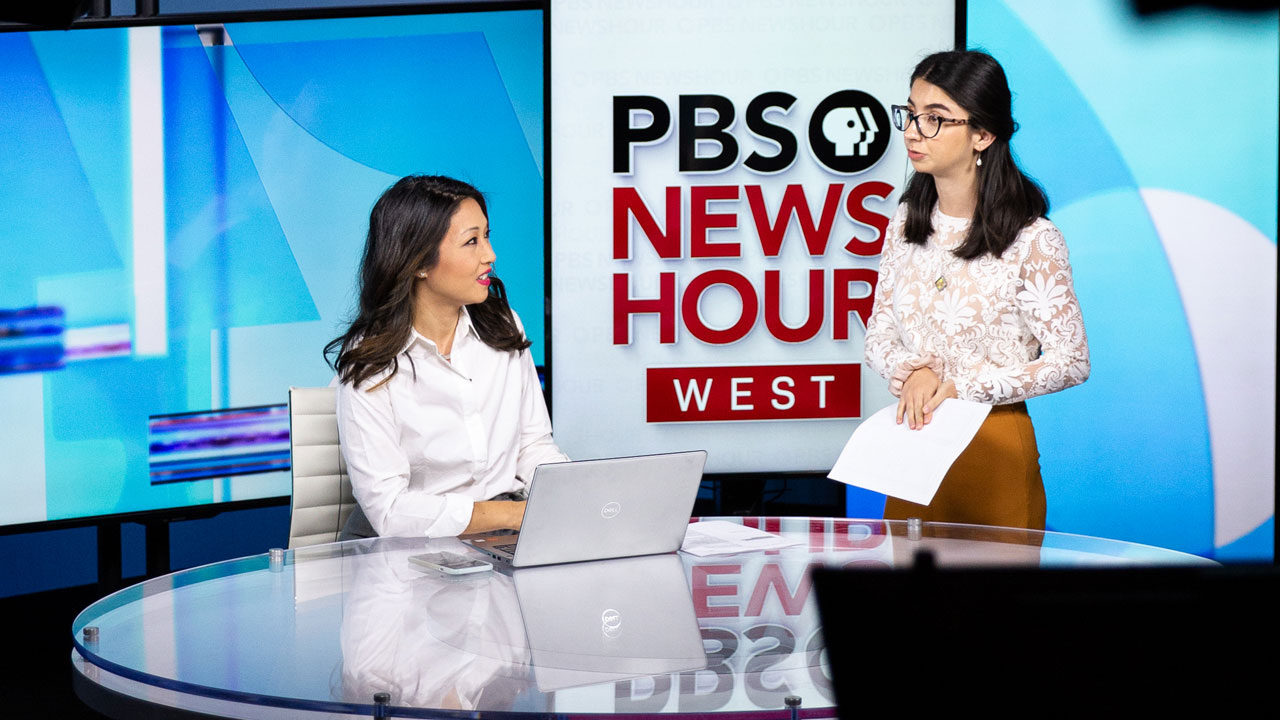 Two journalists talk on the set of PBS NewsHour West.