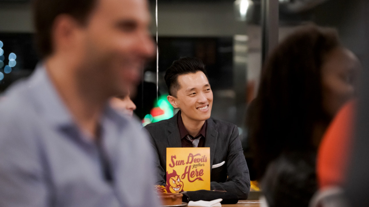 A student smiles amongst his peers at a Sun Devil event.