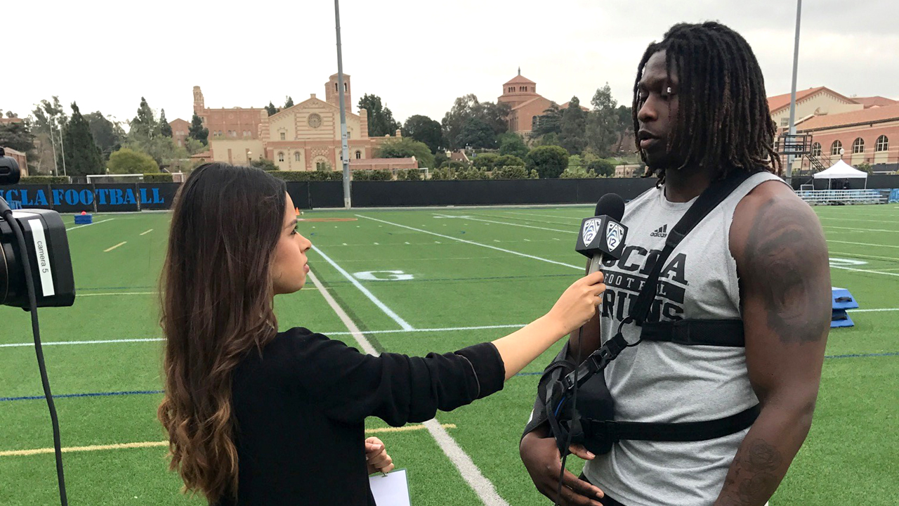 A student reporter interviews an athlete at a football field.