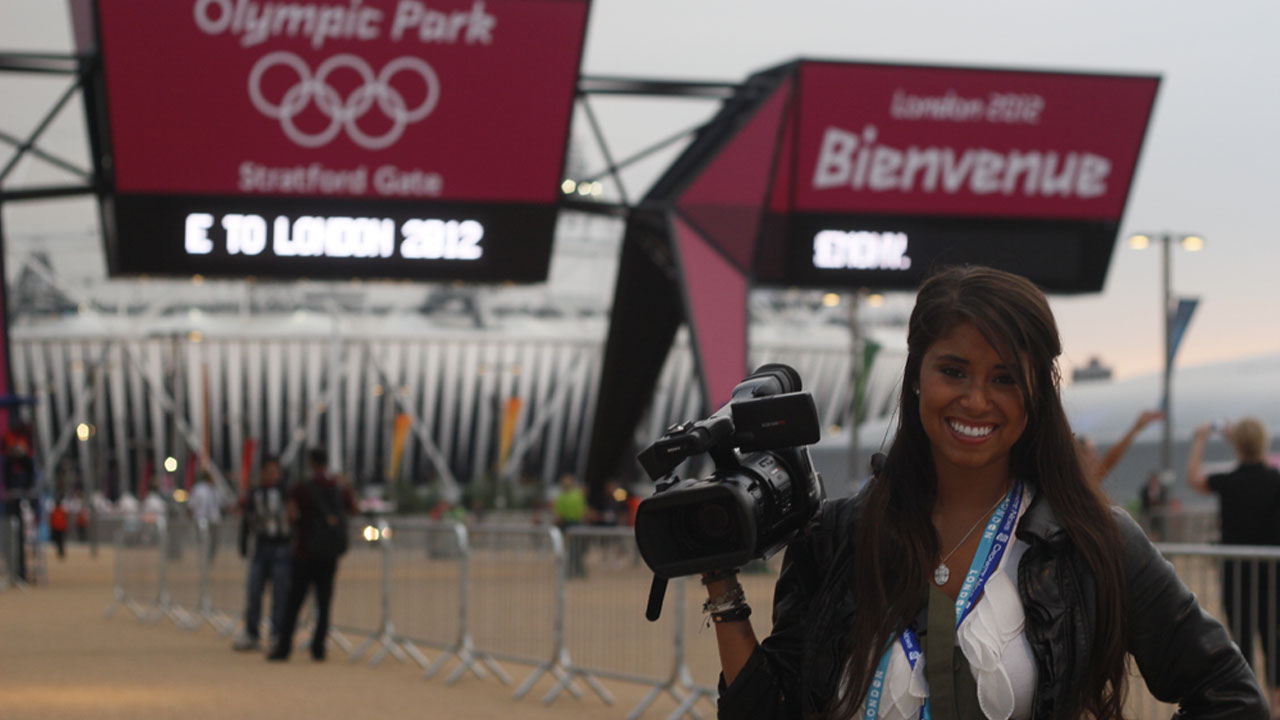 A student reporter holds a camer at the 2012 Olympics.