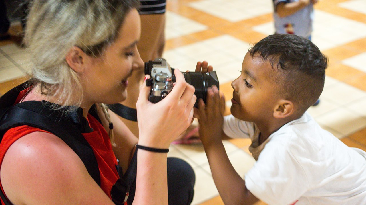 A student photographer takes a photo of a child.
