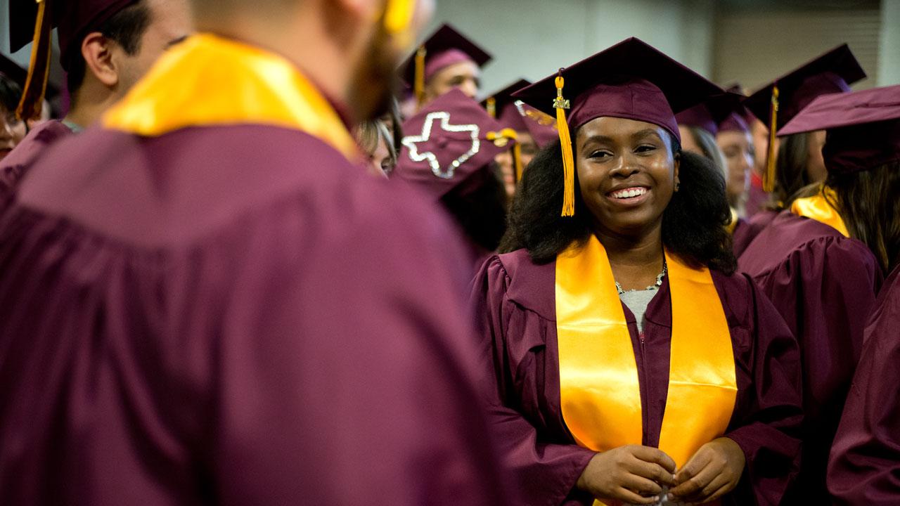Graduates stand in their regalia.