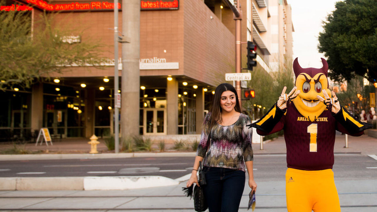 A student walks in Downtown Phoenix with Sparky, the ASU mascot.