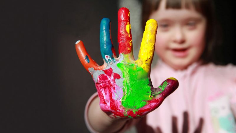 A girl a person who has Down syndrome with her hand out painted colorfully.