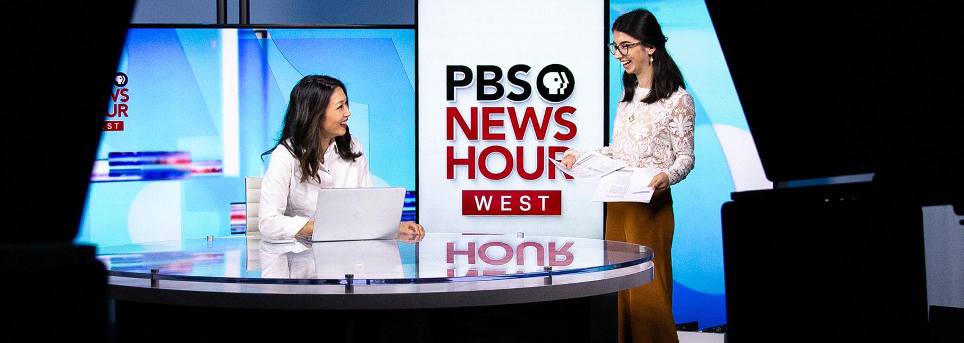 Cronkite student Muska Olumi (right) delivers a script to anchor Stephanie Sy before the PBS NewsHour West show. Photo by Ellen O'Brien
