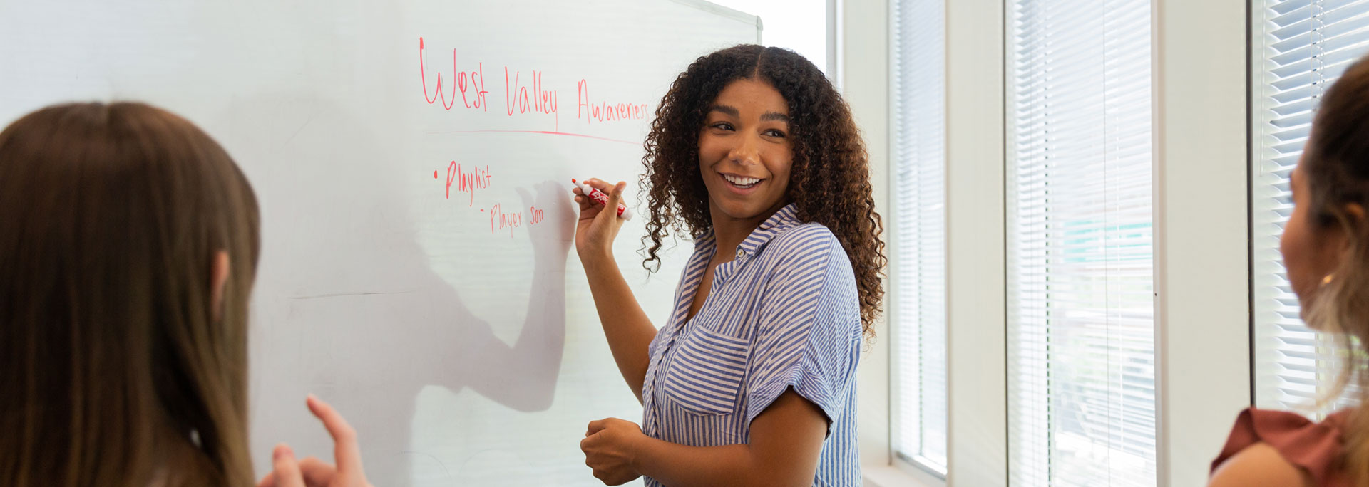 Public Relations Lab students strategize using a whiteboard.