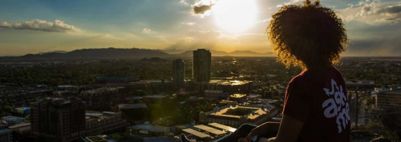 ASU student sits on A-Mountain viewing ASU campus in downtown Tempe