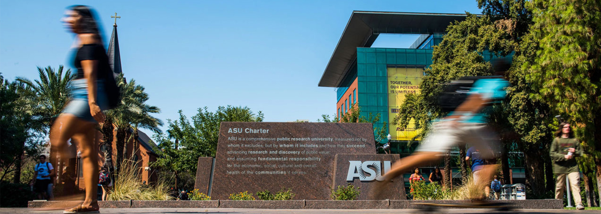 Students walk in front of the ASU Charter sign.