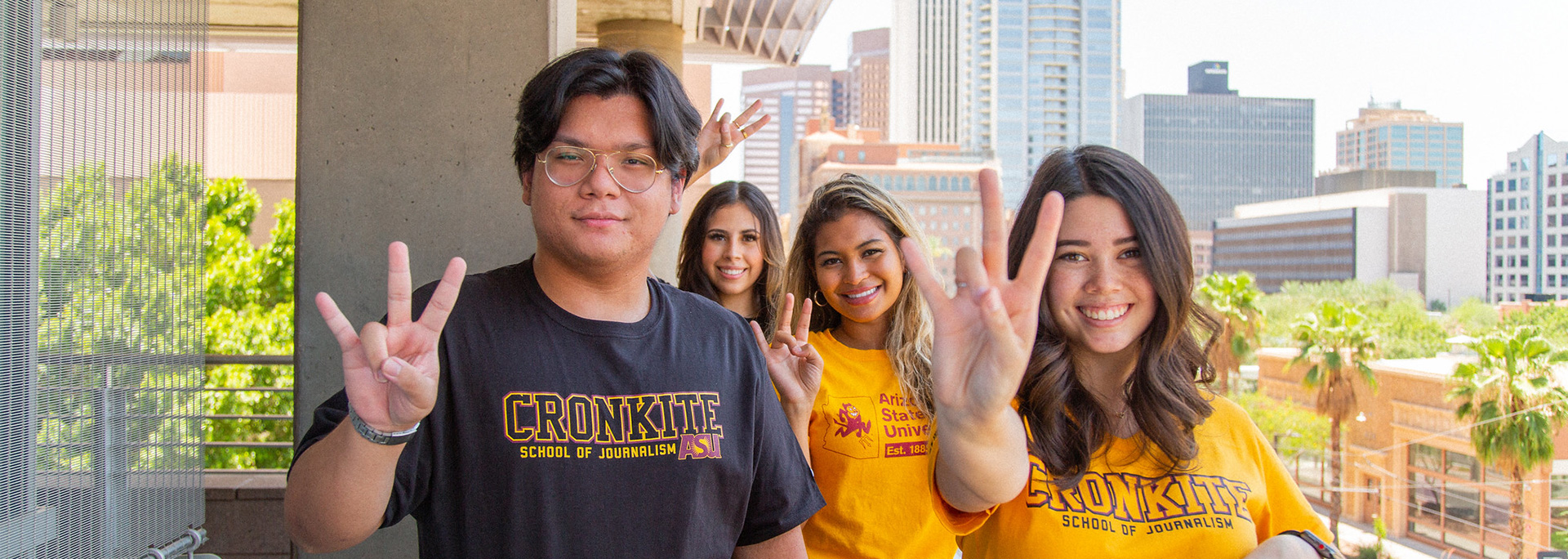 Four Cronkite students hold up the pitchfork hand sign.