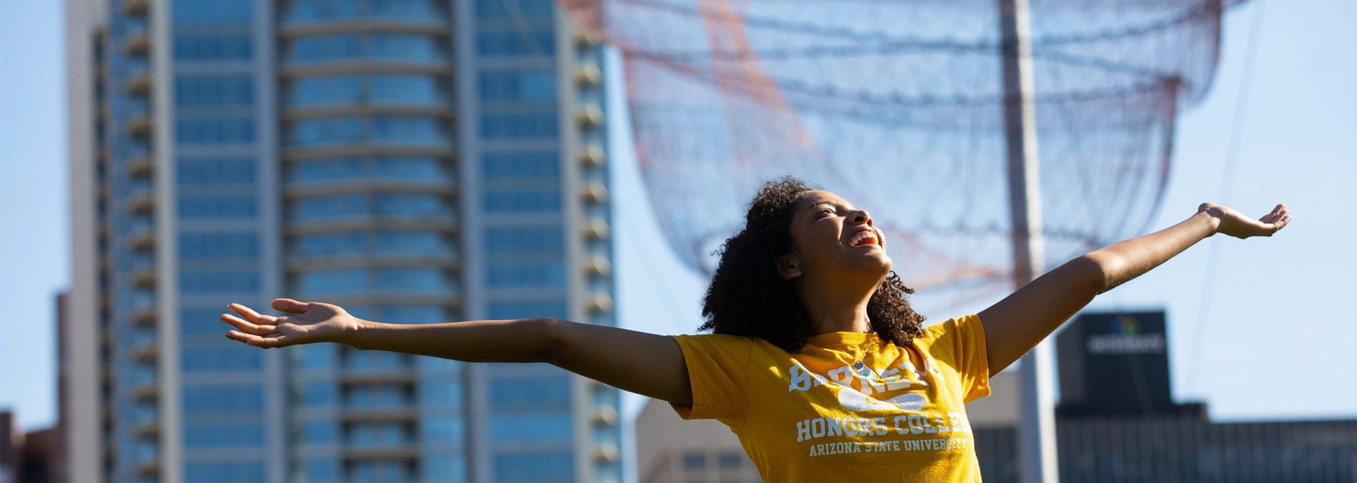 An ASU student stands with their arms out in Civic Space Park.