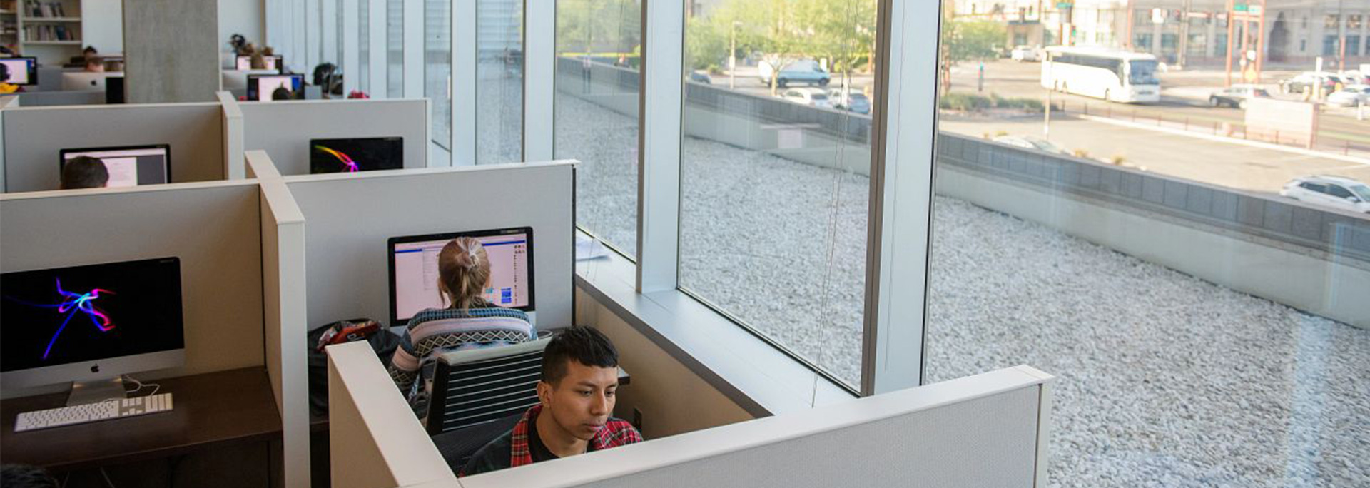 Students work on computers in a dedicated editing space.