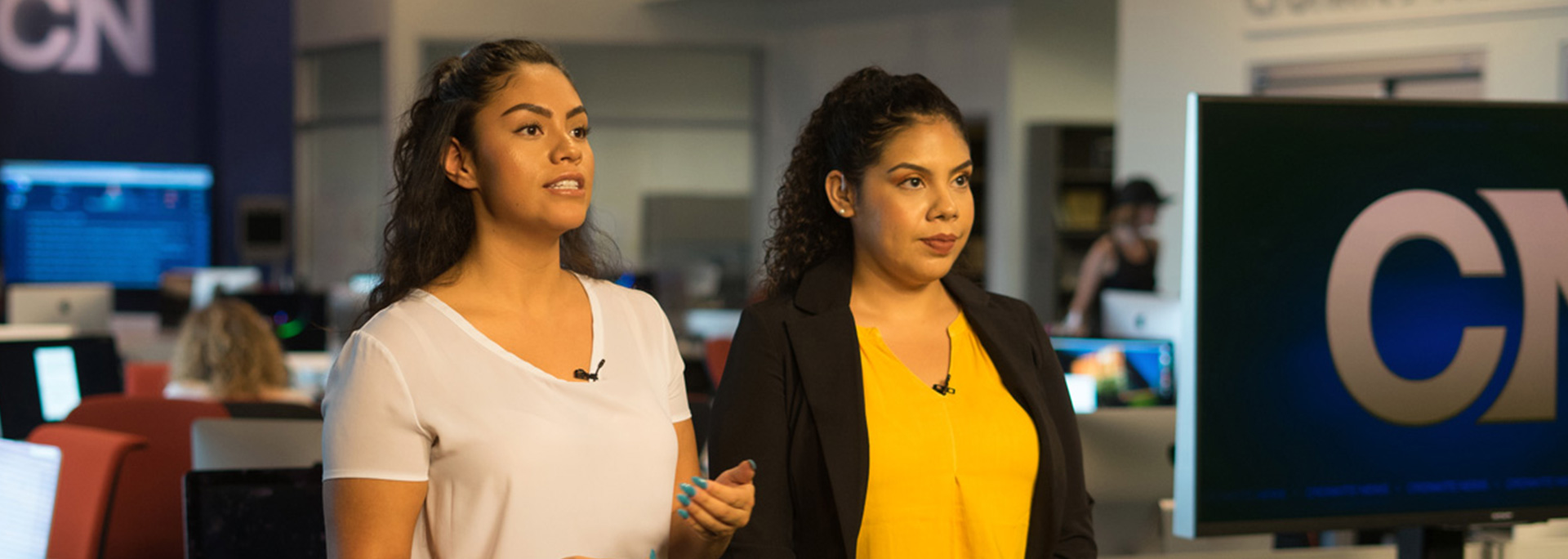 Two Cronkite Noticias students report from the newsroom.
