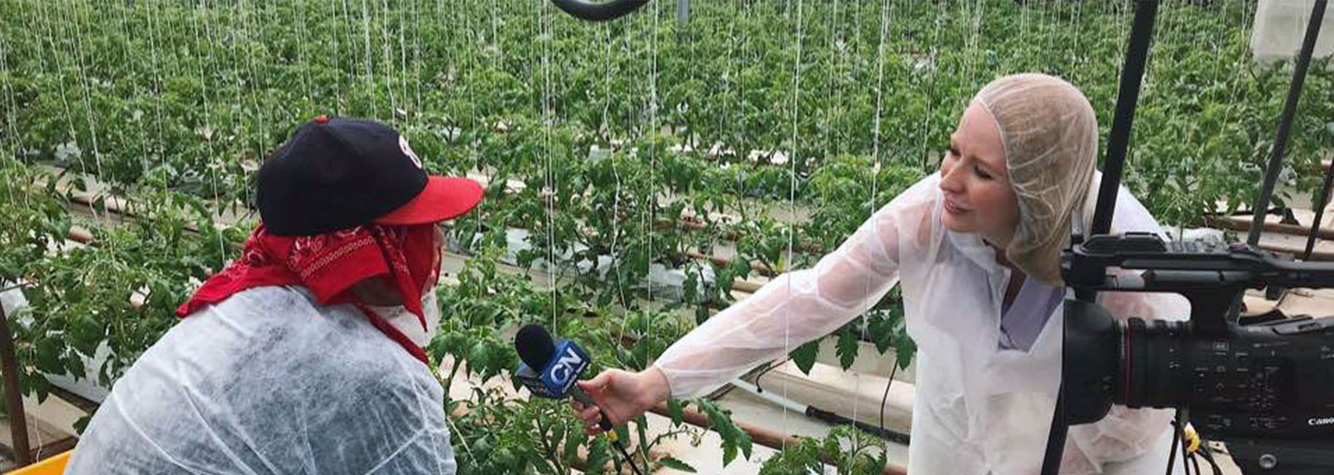 A student reporter interviews a worker outdoors in a field.