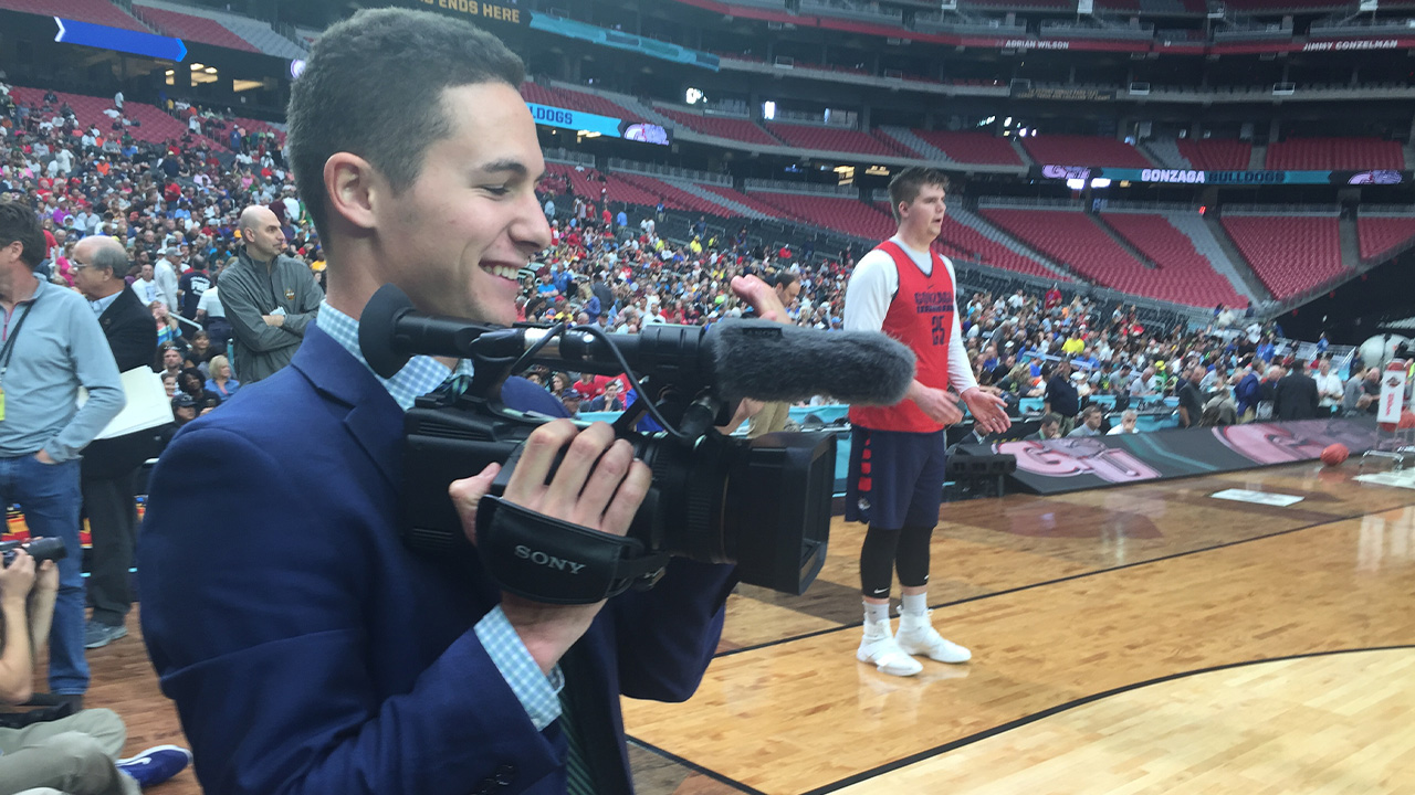 A sports student films a basketball game.
