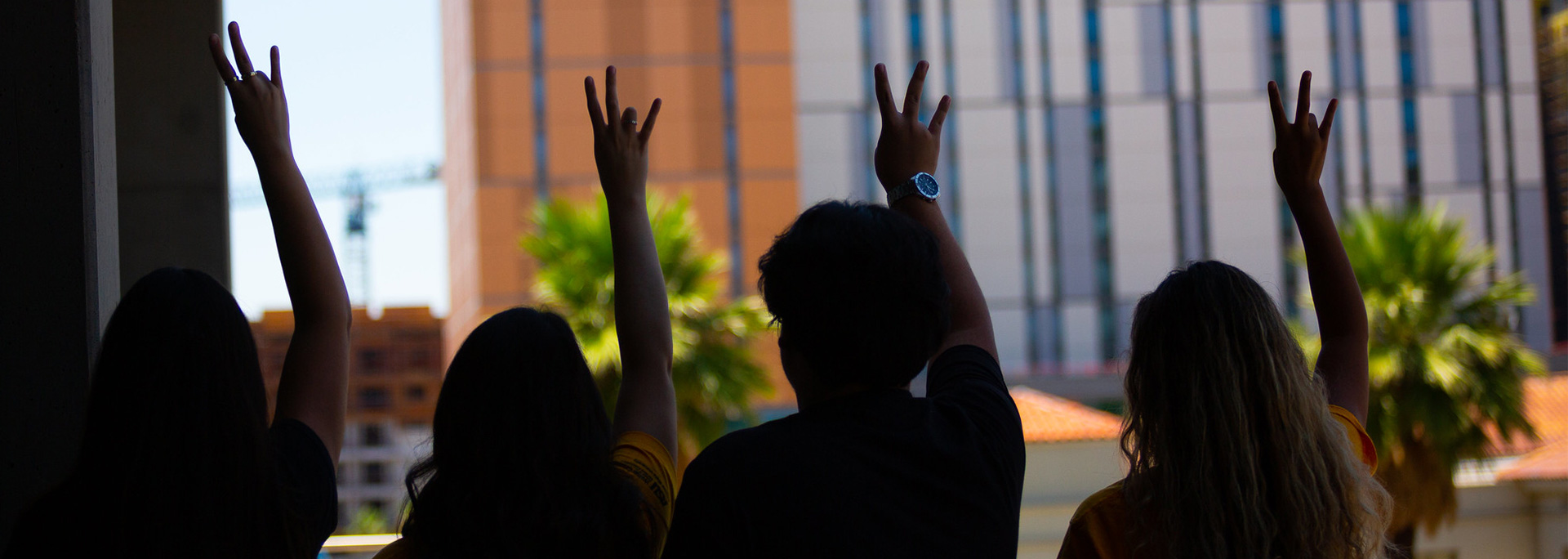 The silhouettes of four cronkite students holding up the ASU pitchfork.