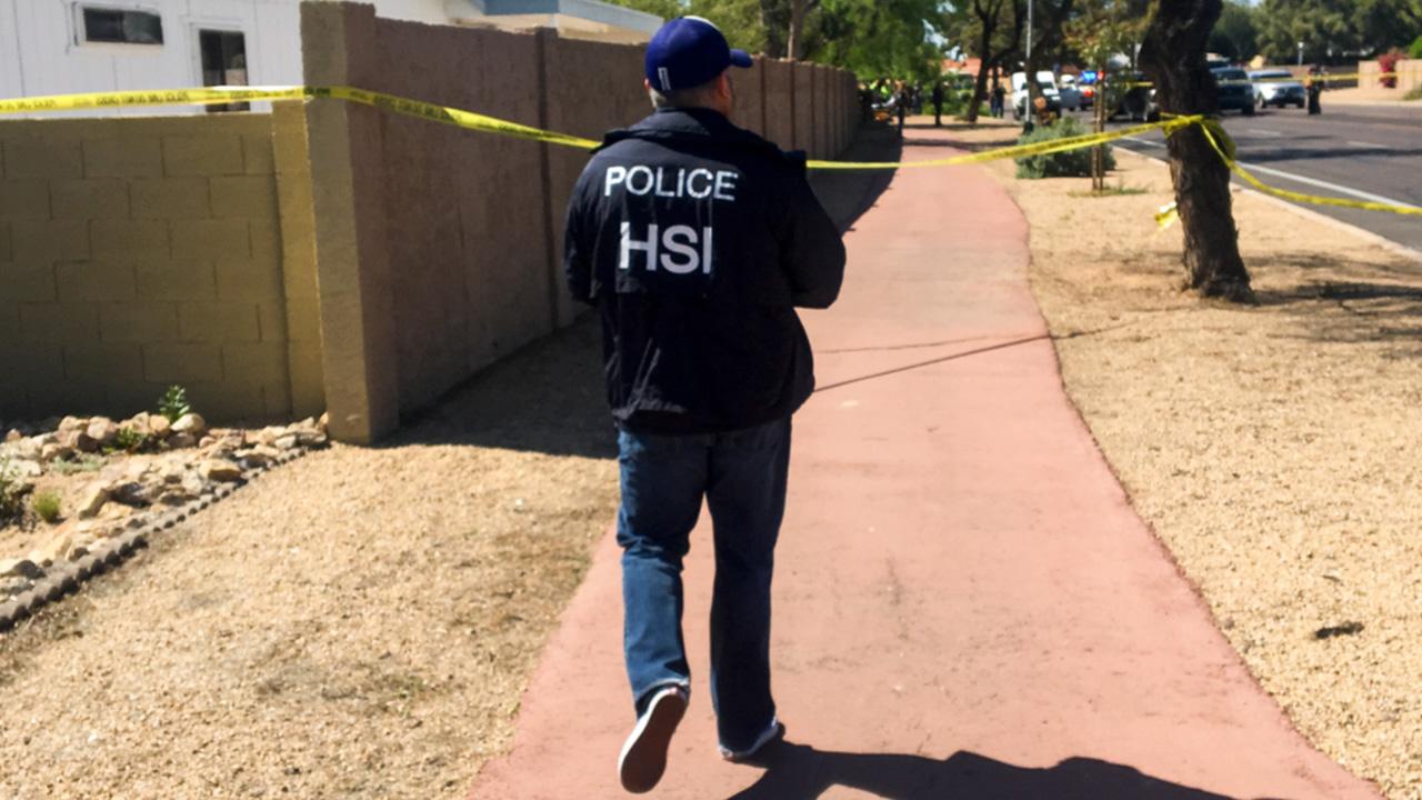 An officer walks along a sidewalk.