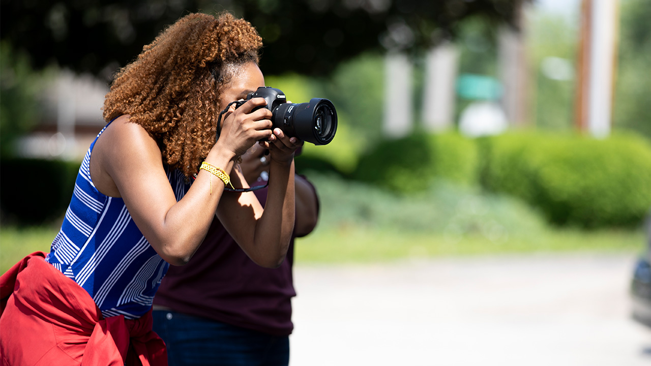 A News21 student holds up a camera to take a picture.