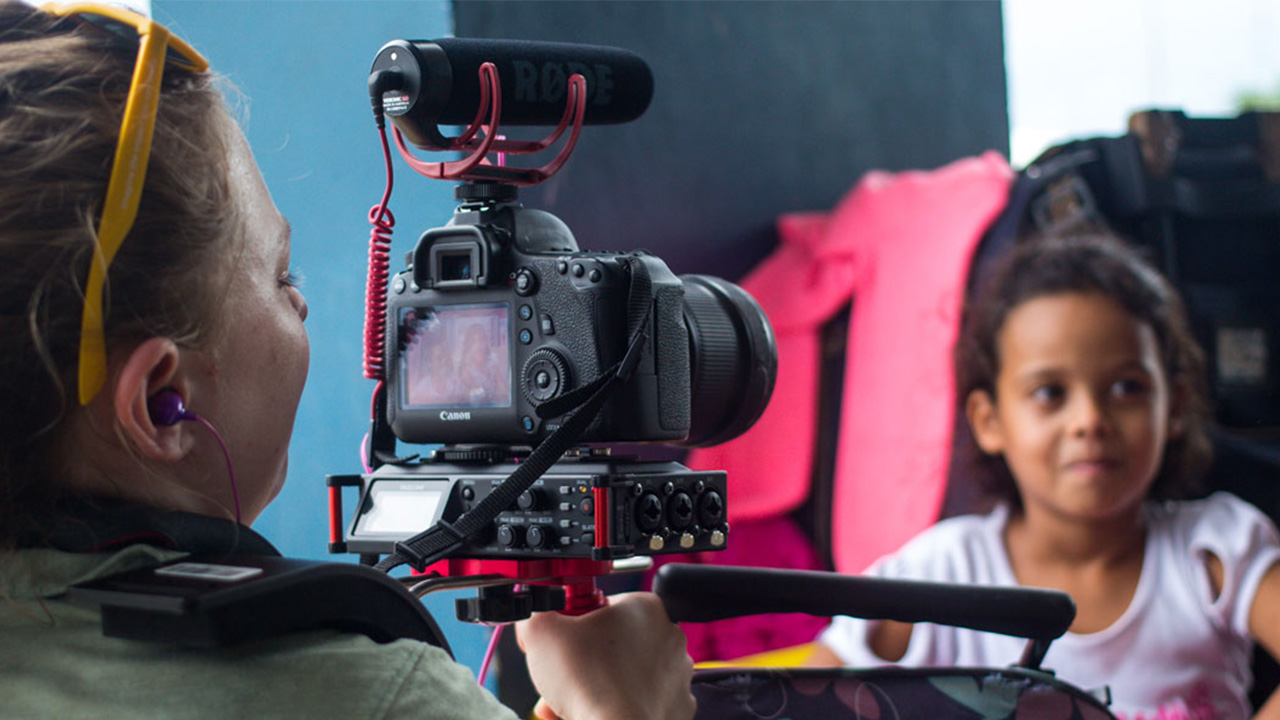 A student films films children on a professional camera.